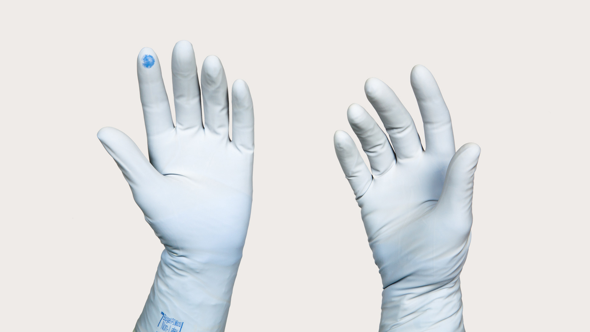 two hands gloved in Puncture Indication System gloves